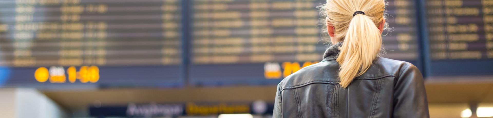 Flugverspätung: Flughafen - Anzeigetafel - Frau - Emotion