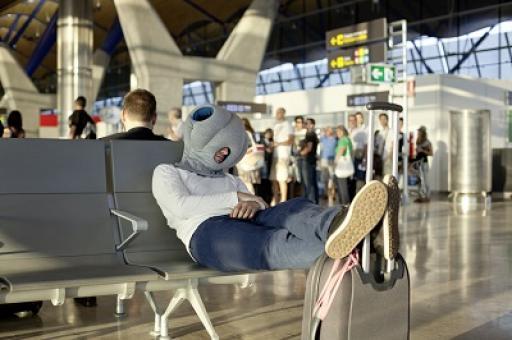 Mann mit Ostrich Pillow am Flughafen